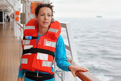 Woman Wearing a Life Vest on a Cruise Ship Deck (Photo: Pavel L Photo and Video/Shutterstock)